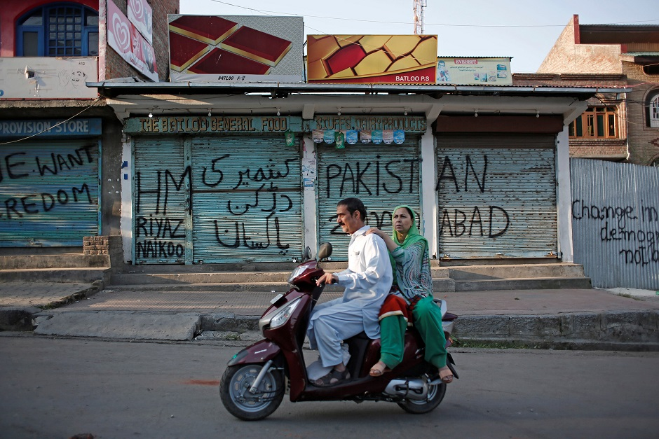 kashmiris ride on a scooter past the closed shops painted with graffiti during restrictions after scrapping of the special constitutional status for kashmir by the indian government in srinagar photo reuters