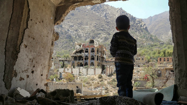 A photo taken on March 18, 2018, shows a Yemeni child looking out at buildings that were damaged in an air strike in the southern Yemeni city of Taez. PHOTO: AFP