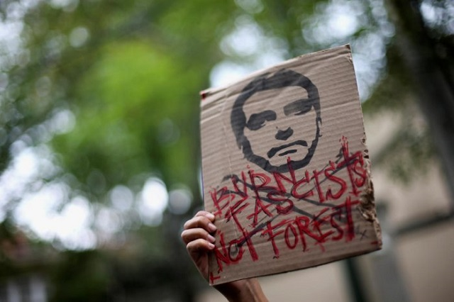An activist holds a sign with an illustration of Brazilian President Jair Bolsonaro as they demand more Amazon rainforest protection at the embassy of Brazil in Mexico City, Mexico August 23, 2019. (Photo: REUTERS)