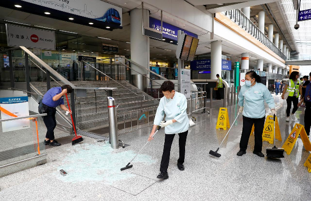 Staff clean up glass from a glass door broken by protesters inside Hong Kong International Airport. PHOTO: Reuters