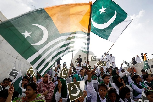 attendees wave pakistan 039 s national flag and kashmir 039 s flag to express solidarity with the people of kashmir at the mausoleum of muhammad ali jinnah photo reuters
