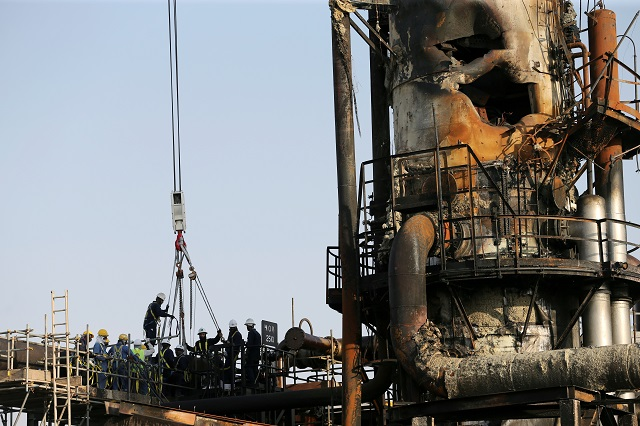 Workers are seen at the damaged site of Saudi Aramco oil facility in Abqaiq, Saudi Arabia. PHOTO: REUTERS/FILE
