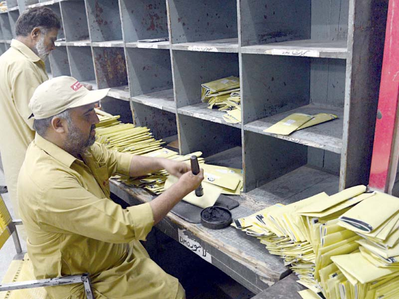 Workers sort mail at a post office in Lahore. PHOTO: ONLINE