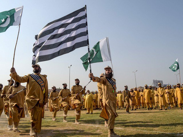 JUI-F activists hold the Pakistani and their party flags as they prepare for Azadi March in Peshawar on October 13, 2019. PHOTO: AFP