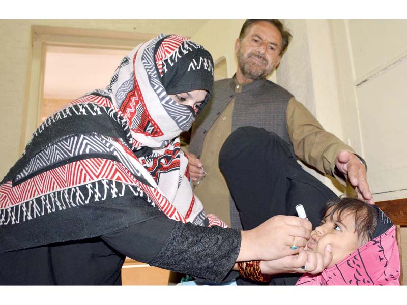 A lady health worker administers polio drops to a child. PHOTO: INP