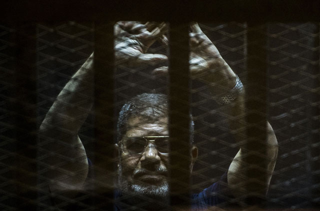 A file picture taken on June 2, 2015 shows ousted Egyptian president Mohamed Morsi gesturing from the defendants cage as he attends his trial at the police academy on the outskirts of the capital Cairo. PHOTO: AFP