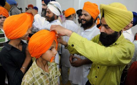 Sikh children have turbans tied over their heads during a gathering for World Turban Day. PHOTO: AFP/FILE.