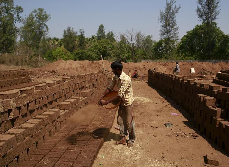 a labourer throws mud on bricks kept for drying at a kiln photo reuters