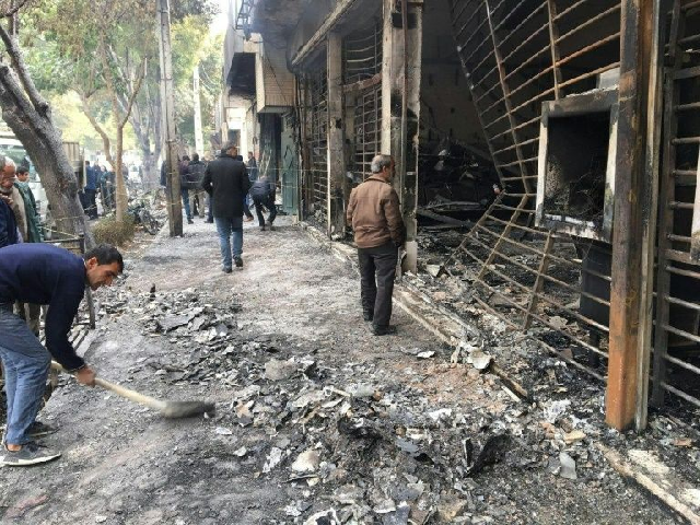 Iranians walk past a bank that was set on fire by protesters during a demonstration against a rise in gasoline prices in Isfahan on November 17. PHOTO: AFP