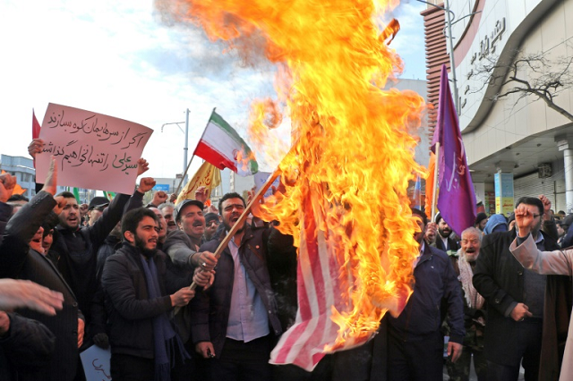Iranian men burn a US flag during a protest in support of the Islamic republic's government and supreme leader Ayatollah Ali Khamenei. PHOTO: AFP