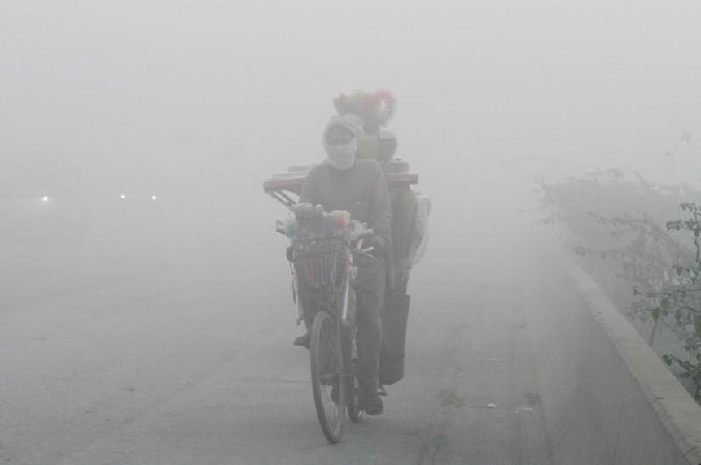 a man rides a bicycle on a smoggy morning in lahore photo reuters