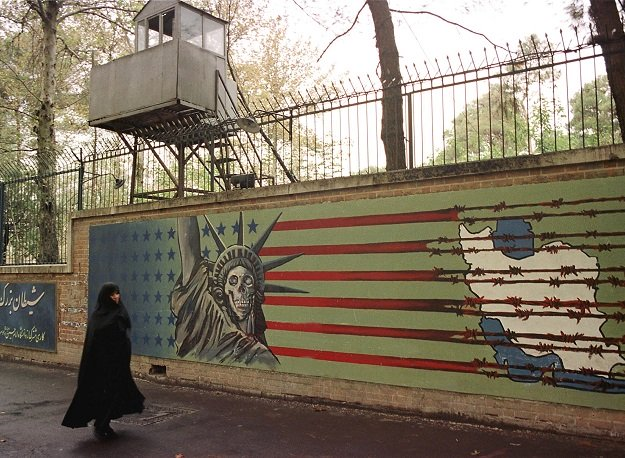a file photo taken on november 03 1999 shows an iranian woman walking past an anti us mural at the former us embassy in tehran photo afp
