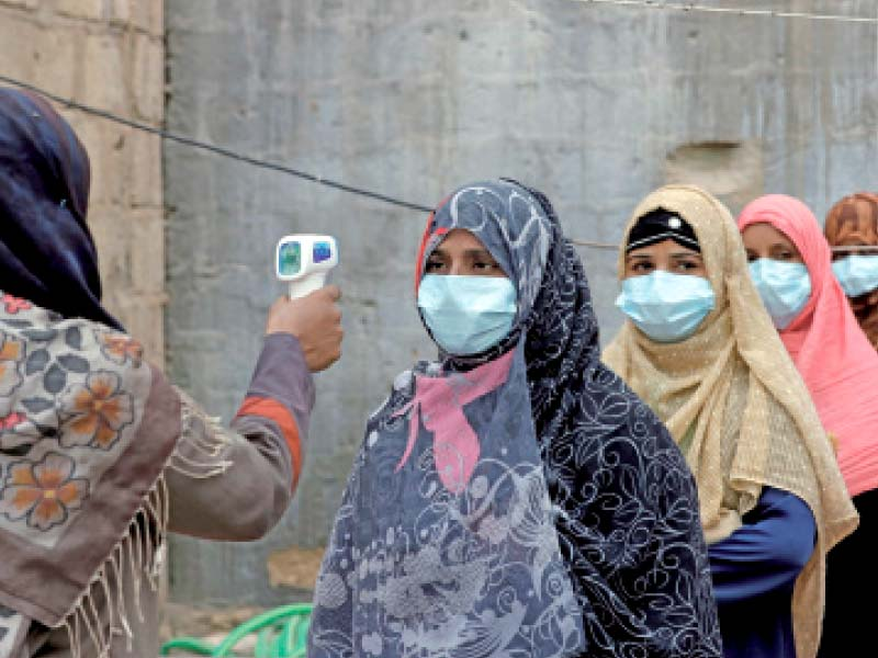 a health official checks polio workers wearing masks for fever before the immunisation drive photo reuters file
