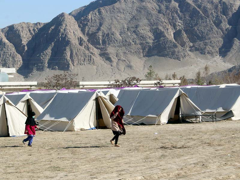 young pilgrims walk in front of temporary tents at pak iran border area in taftan photo online