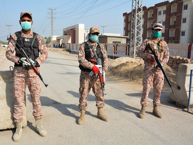 Soldiers wearing facemasks stand guard on road leading to a quarantine faciltity (R) for people returning from Iran via the Pakistan-Iran border town of Taftan to prevent the spread the COVID-19 coronavirus, in Sukkur in southern Sindh province on March 17, 2020. PHOTO: AFP