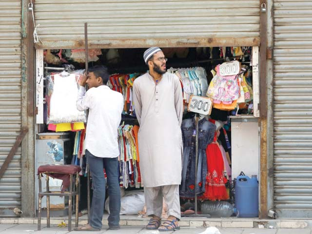 Shopkeepers furtively opened their stores with half or even fully-closed shutters in several markets on Wednesday, against the Sindh gov-ernment's orders. PHOTO: REUTERS