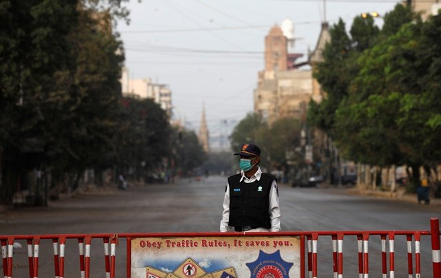 A traffic police officer stands with a barrier on a deserted road of a business district during a partial lockdown after Pakistan shut all markets, public places and discouraged large gatherings amid an outbreak of coronavirus disease (COVID-19), in Karachi. PHOTO: REUTERS