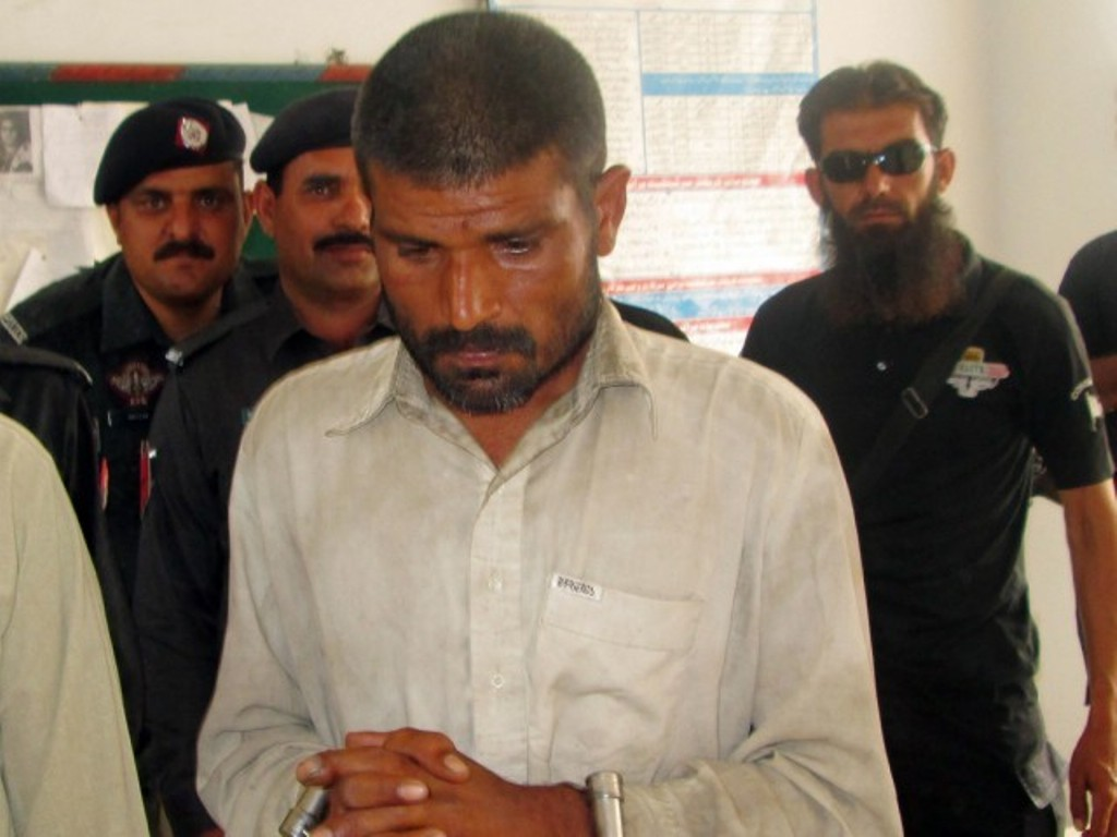 Arif, arrested on suspicion of cannibalism, is escorted to a police station in Bhakkar district on April 14, 2014. PHOTO: FILE/AFP