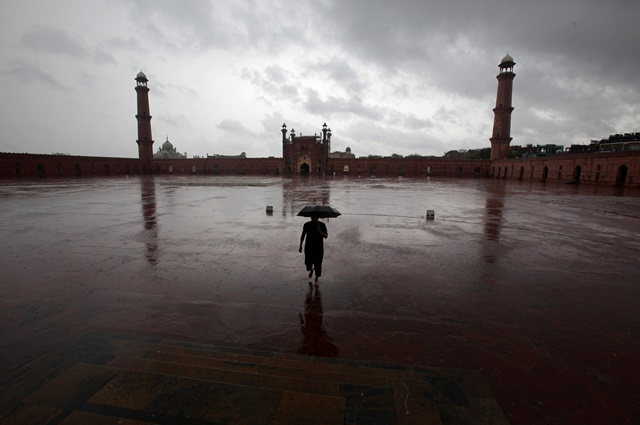 a man with an umbrella walks on the floor of the badshahi mosque to attend friday prayer despite the lockdown after pakistan shut all markets and public places and discouraged large gatherings amid an outbreak of coronavirus disease covid 19 in lahore photo reuters