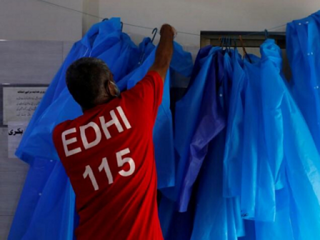 A volunteer of the Edhi Foundation, a non-profit social welfare programme, hangs up raincoats to be used to handle suspected carriers of the coronavirus disease (COVID-19), in Karachi, Pakistan March 26, 2020. PHOTO: REUTERS