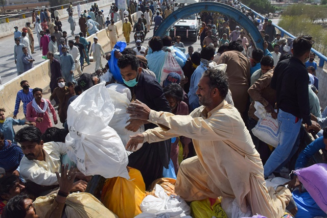 People gather to receive ration handouts from a charity truck, during a lockdown after Pakistan shut all markets, public places and discouraged large gatherings amid an outbreak of coronavirus disease (COVID-19), in Hyderabad, Pakistan March 30, 2020. REUTERS