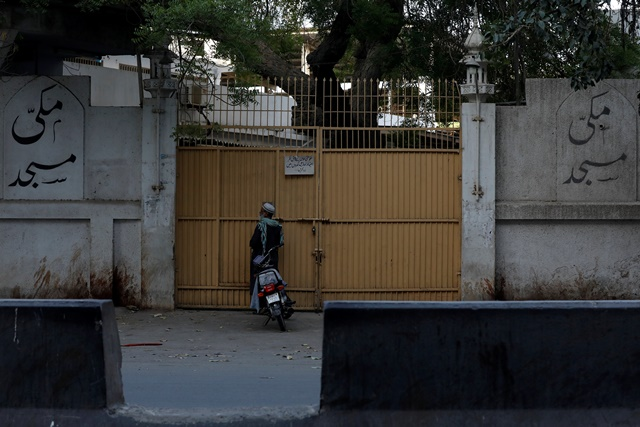 A man stands at the closed entrance of the Makki Masjid Tablighi center, after the government ordered to quarantine the center, following the outbreak of coronavirus disease (COVID-19), in Karachi. PHOTO: REUTERS