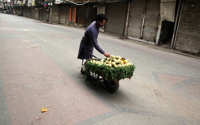a-fruit-vendor-waits-for-customers-as-he-sells-guava-from-a-wheelbarrow-along-a-closed-market-during-a-lockdown-following-an-outbreak-of-coronavirus-disease-covid-19-in-lahore-photo-reuters