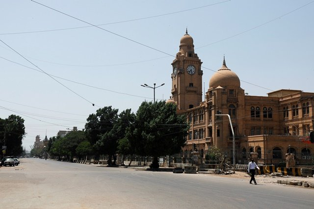 a man walks on the deserted road past the karachi municipal corporation kmc building during a lockdown after pakistan shut all markets public places and discouraged large gatherings amid an outbreak of coronavirus disease covid 19 in karachi photo reuters