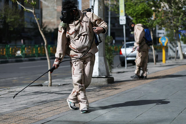 Volunteers from Basij forces wearing protective suits and face masks spray disinfectant on the streets, amid the coronavirus disease (COVID-19) fears, in Tehran, Iran April 3, 2020. PHOTO: REUTERS