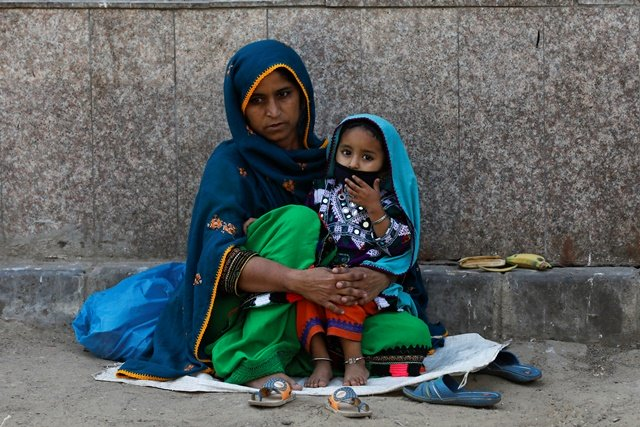 three year old nadia wears protective mask sitting on her mother 039 s lap as they are waiting to visit an ailing family member outside a hospital during a lockdown after pakistan shut all markets public places and discouraged large gatherings amid an outbreak of coronavirus disease covid 19 in karachi photo reuters