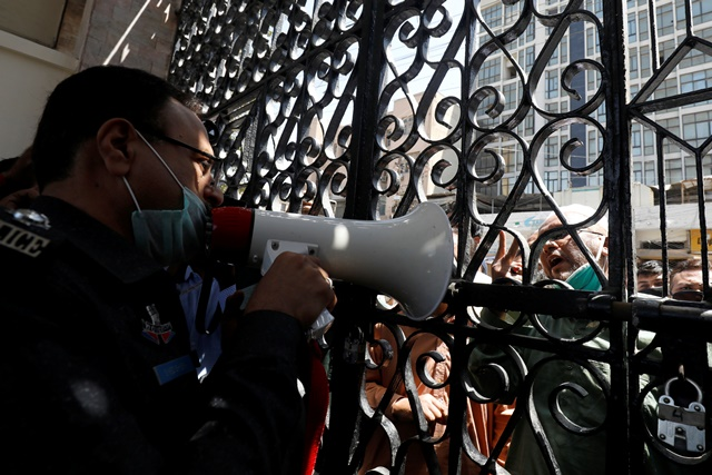 a police officer uses a megaphone requesting people to go and pray at home at the locked entrance gate of a mosque during a lockdown after pakistan shut all markets public places and discouraged large gatherings amid an outbreak of coronavirus disease covid 19 in karachi pakistan march 27 2020 reuters