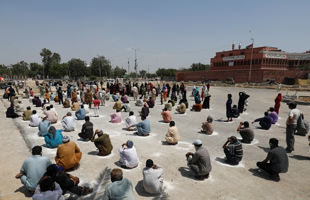 people sit on the ground in circles drawn with chalk to maintain safe distance as they wait to receive sacks of ration handouts from a distribution point of a charity during a partial lockdown after pakistan shut all markets public places and discouraged large gatherings amid an outbreak of coronavirus disease covid 19 in karachi pakistan march 29 2020 reuters akhtar soomro