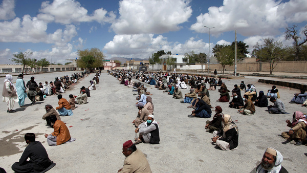 people sit on the ground as they wait to receive sacks of ration handouts from a distribution point of a charity during a lockdown after pakistan shut all markets public places and discouraged large gatherings amid an outbreak of coronavirus disease covid 19 in quetta pakistan march 31 2020 photo reuters