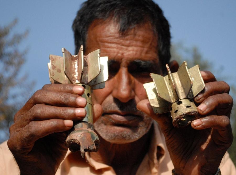 a pakistani man shows remains of an indian mortar shells photo afp file