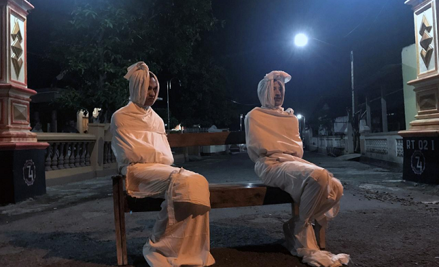 volunteers deri setyawan 25 and septian febriyanto 26 sit on a bench as they play the role of 039 pocong 039 or known as 039 shroud ghost 039 to make people stay at home amid the spread of coronavirus disease covid 19 outside the gate of kepuh village in sukoharjo regency central java province indonesia april 1 2020 photo reuters