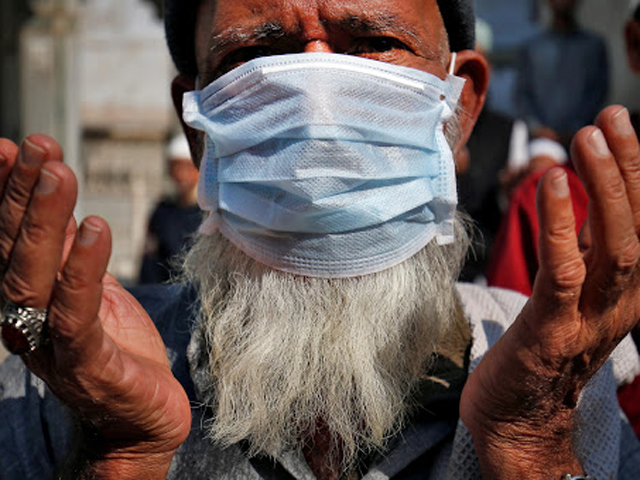 a muslim wearing a mask prays for the victims of coronavirus at a mosque in ahmedabad india photo reuters file