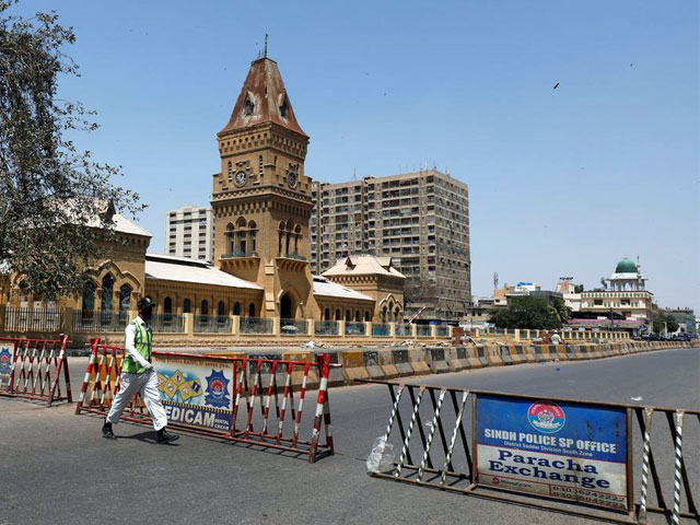 a traffic police officer walks past barriers used to block the road in front of the british era empress market building during a lockdown after pakistan shut all markets public places and discouraged large gatherings amid an outbreak of coronavirus disease photo reuters