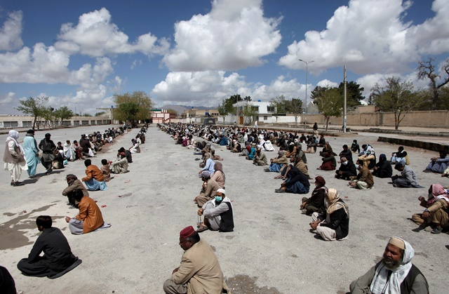 people sit on the ground as they wait to receive sacks of ration handouts from a distribution point of a charity during a lockdown after pakistan shut all markets public places and discouraged large gatherings amid an outbreak of coronavirus disease covid 19 in quetta pakistan march 31 2020 reuters naseer ahmed