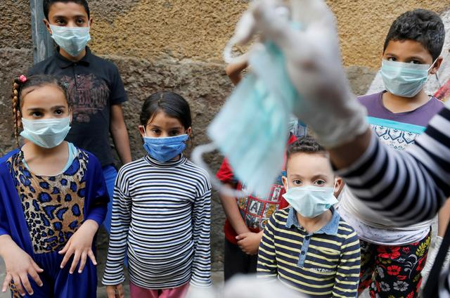 egyptian clown ahmed naser performs to entertain and help children to put on face masks as a preventive measure amid concerns about the spread of the coronavirus disease covid 19 in darb al ban district at islamic cairo egypt photo reuters file