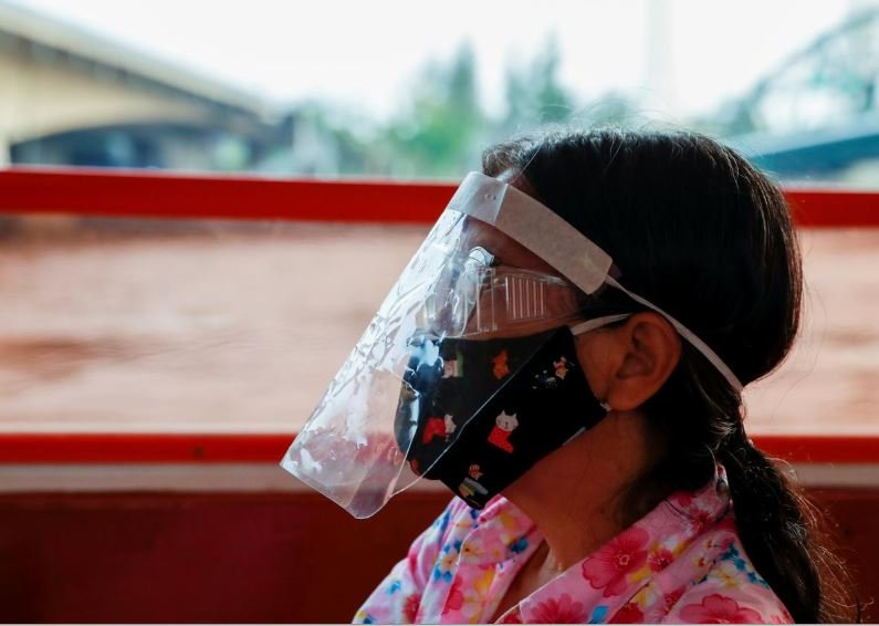 a woman wears a protective face mask while commuting by boat at the chao phraya river during the coronavirus disease covid 19 outbreak in bangkok thailand photo afp