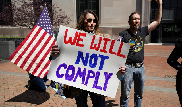 a protestor carries a sign reading quot we will not comply quot during a demonstration outside the virginia state capitol to protest virginia 039 s stay at home order and business closures in the wake of the coronavirus disease covid 19 outbreak in richmond virginia us april 16 2020 photo reuters