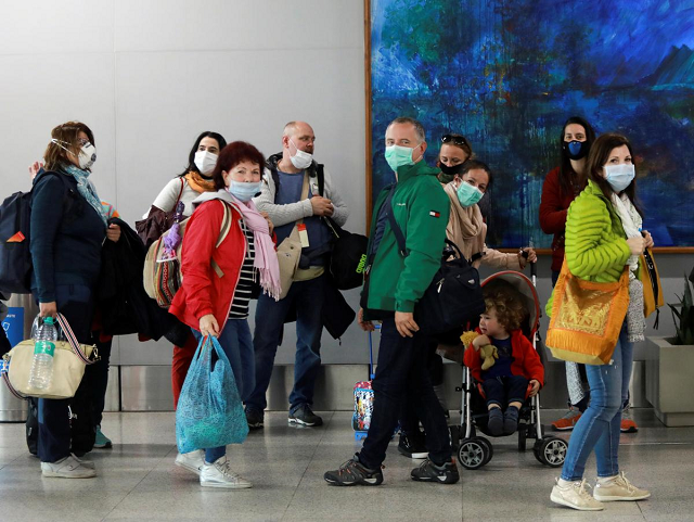 passengers wearing protective masks arrive to collect their luggage inside an airport following an outbreak of the coronavirus disease covid 19 in new delhi india march 14 2020 photo reuters