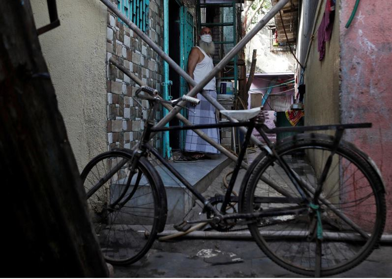 a man stands behind a makeshift barricade set up to stop people from entering a lane during a nationwide lockdown in india to slow the spread of covid 19 in dharavi one of asia 039 s largest slums during the coronavirus disease outbreak in mumbai india photo reuters