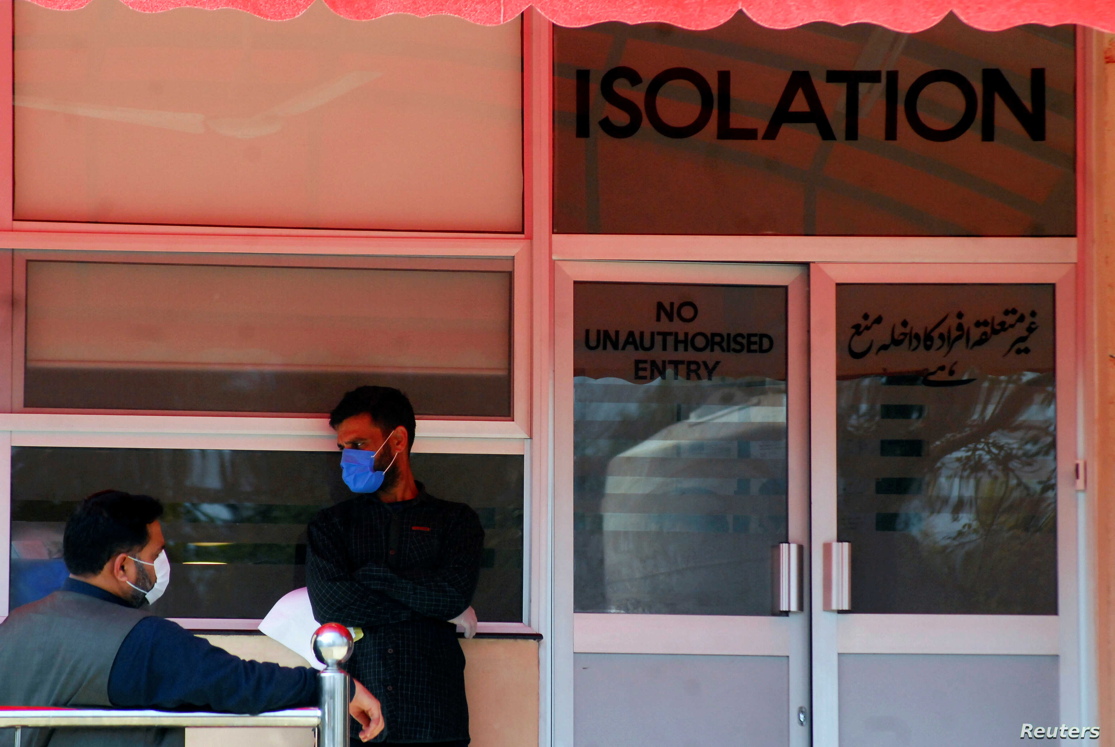 men wear protective mask as a preventive measure against coronavirus as they stand outside the isolation ward at the pakistan institute of medial sciences in islamabad photo reuters