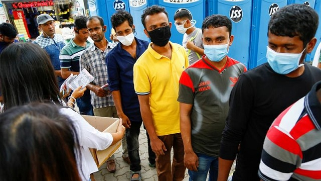 migrant workers mostly from bangladesh queue to collect free masks and get their temperatures checked in singapore photo reuters