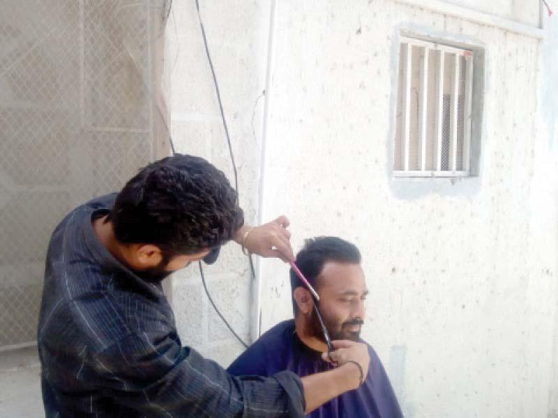 a barber giving a customer haircut at his home photo express