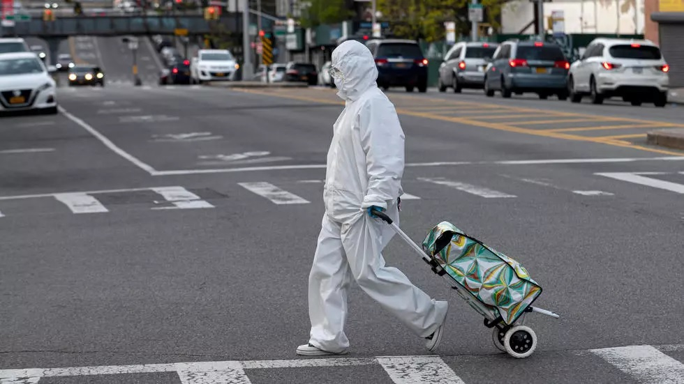 a woman wearing a hazmat suit and googles pulls her grocery cart through new york city on april 20 2020 photo afp