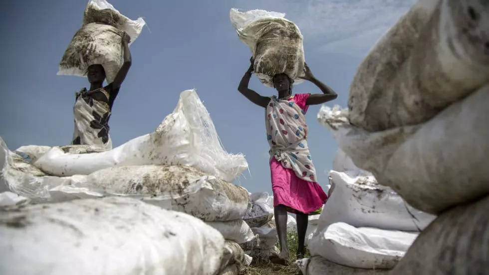 women carry sacks of food airdropped by the world food programme and distributed by the ngo oxfam in padding near lankien jonglei south sudan on july 3 2017 photo afp