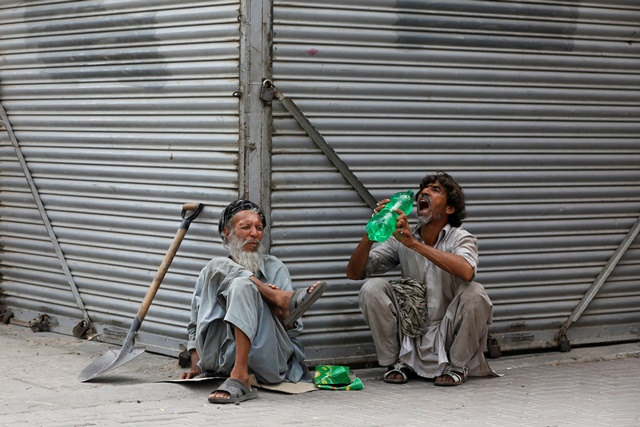 FILE PHOTO: Daily wage laborers, wait for work as they sit outside closed shops, during lockdown amid the outbreak of coronavirus disease (COVID-19), at a market in Karachi, Pakistan April 14, 2020. REUTERS/Akhtar Soomro/File Photo