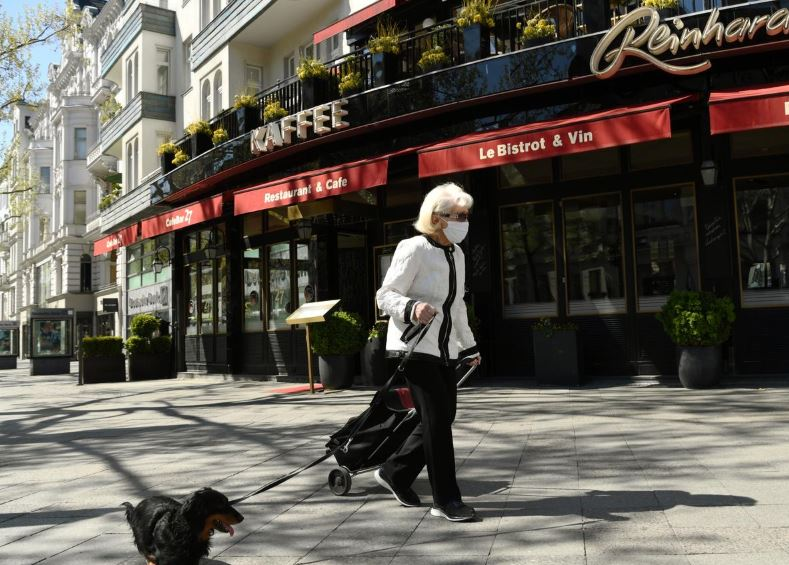 a woman wearing a protective mask walks with a dog at the shopping street quot kurfuerstendamm quot as the spread of the coronavirus disease covid 19 continues in berlin germany april 23 2020 photo reuters